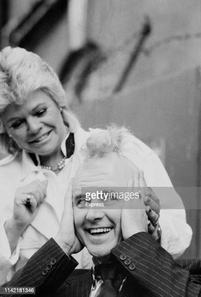 British television presenter Judith Chalmers with British Liberal Democrat politician David Steel in a Mohawk hairstyle, UK, 21st February 1984.