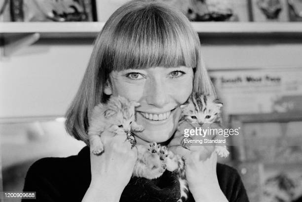 British television presenter Lesley Judd smiling as she holds kittens against either side of her face February 1976