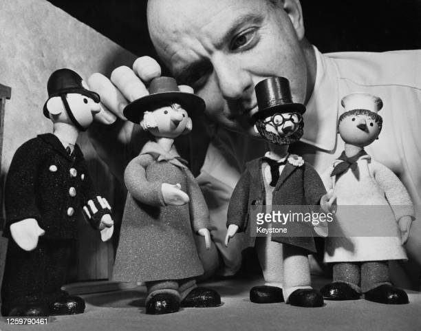 British television producer and puppeteer Gordon Murray adjusts puppets of PC McGarry, Windy Miller, Dr Mopp, and Mickey Murphy during the filming of...