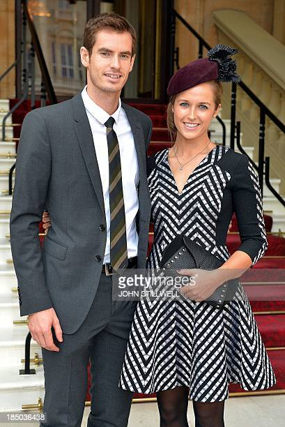 British tennis player Andy Murray and his girlfriend Kim Sears pose for pictures as they arrive at Buckingham Palace in London on October 17 where...