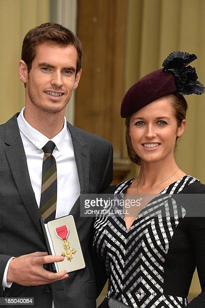 British tennis player Andy Murray and his girlfriend Kim Sears pose for pictures at Buckingham Palace in central London on October 17 after Murray...