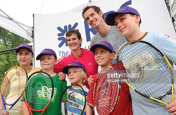 British tennis player Andy Murray and his mother Judy a tennis coach pose with children after giving lessons to young tennis players in Melbourne on...