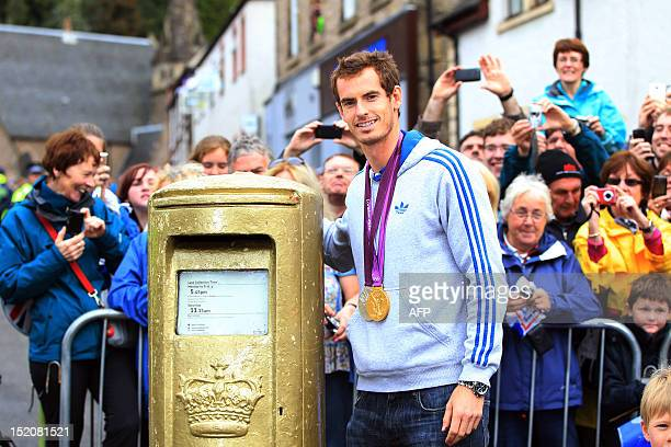British tennis player Andy Murray poses next to a Royal Mail golden post box as he meets with fans in the centre of Dunblane Scotland on September 16...