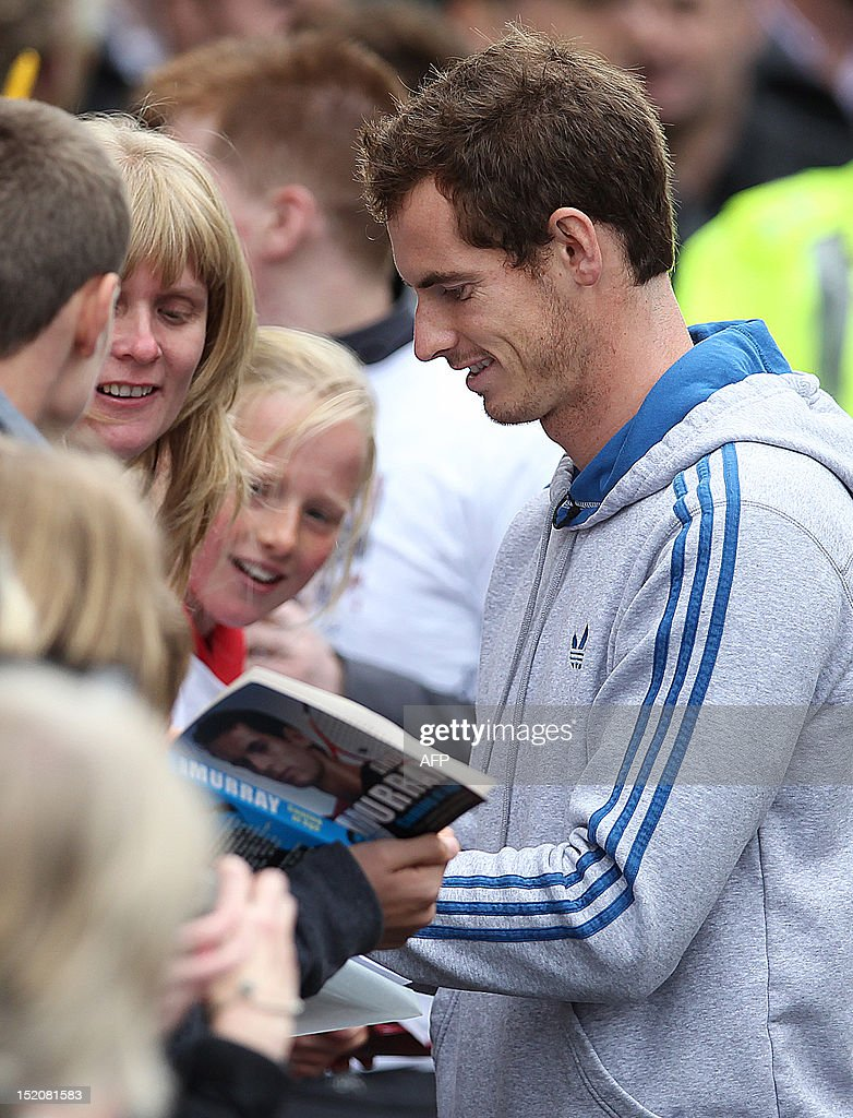British tennis player Andy Murray signs autographs as he meets with fans in the centre of Dunblane, Scotland on September 16, 2012, following his victory in the US Open tennis tournament and gold medal in the London 2012 Olympic Games. Andy Murray, the first British man to win a Grand Slam title in 76 years, received a rapturous welcome in his Scottish home town on Sunday, but admitted that his golden summer was giving him nightmares.