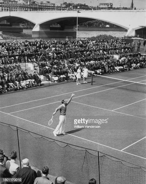 British tennis player Fred Perry of Great Britain prepares to serve against Dan Maskell during a demonstration tennis match for the Central Council...