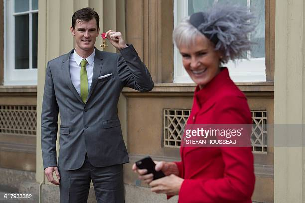 British tennis player Jamie Murray poses as his mother Judy Murray prepares to take a picture at Buckingham Palace in London after he received his...