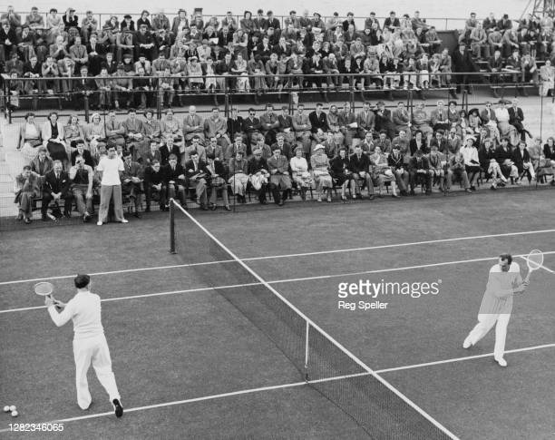 British tennis players Dan Maskell and Fred Perry prepare for a demonstration tennis match on the South Bank tennis court left over from the 1951...