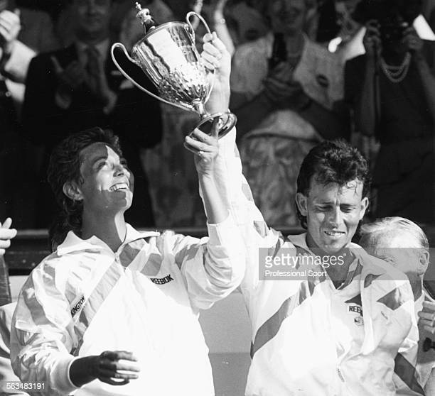 British tennis players Jeremy Bates and Jo Durie hold their trophy in the air in the Royal Box after winning the mixed doubles competition at...