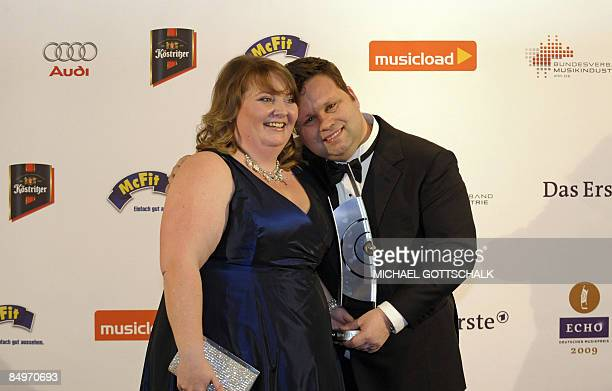 British tenor Paul Potts poses with his wife his wife JulieAnn as he presents his Echo trophy he was awarded in the Best Artist International...