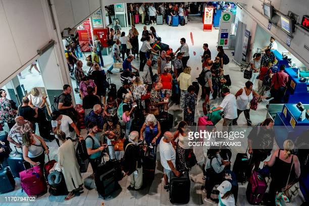 British tourists clients of Thomas Cook travel group wait at counters to be repatriated at the Heraclion airport on the island of Crete on September...
