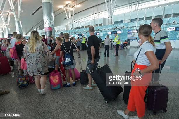 British tourists flying with Thomas Cook queue at the Enfidha International airport on September 23 on the outskirts of Sousse south of the capital...