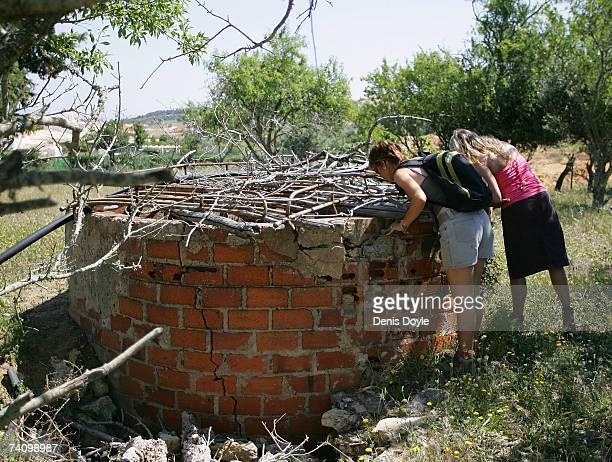 British tourists look down a well while searching for the missing threeyearold girl Madeleine McCann in wasteland on May 8 2007 outside the Algarve...