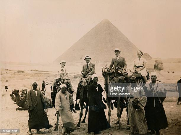 British tourists seated on cammels in front of The Great Pyramid Giza Egypt 1936 From a private album of a passenger who undertook a cruise on the SS...