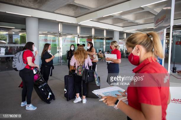 British tourists walk with their luggage outside the airport upon their arrival to Palma de Mallorca on July 27 2020 Tour operator TUI has cancelled...