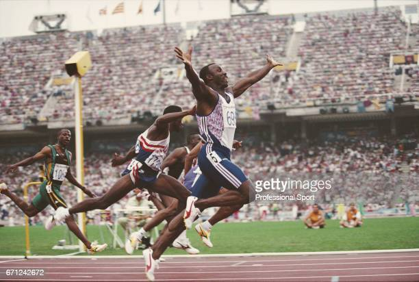 British track and field athlete Linford Christie of the Great Britain team raises his arms in the air as he crosses the finish line in first place to...