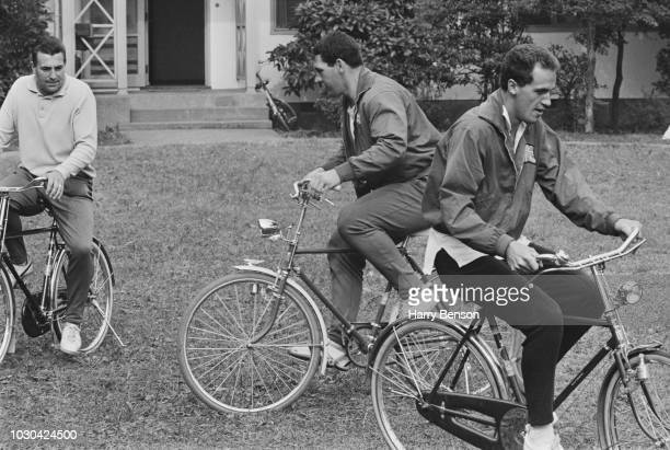 British track and field athlete Mike Lindsay, British Olympic Team coach Ron Pickering , and British athlete Adrian Metcalfe riding bicycles around...