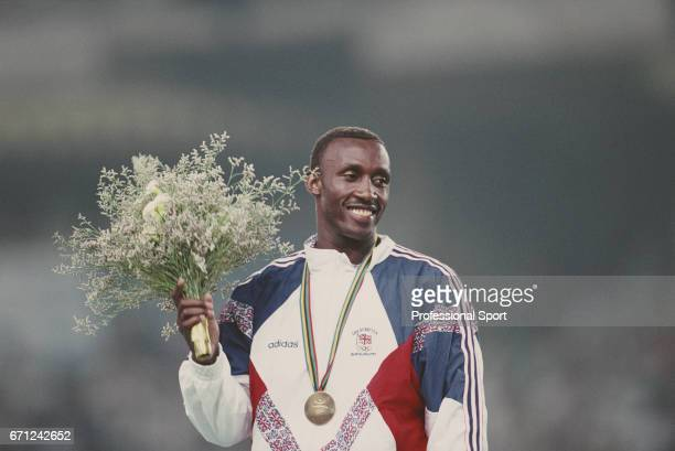 British track athlete Linford Christie of the Great Britain team stands on the medal podium after finishing in first place to win the gold medal in...