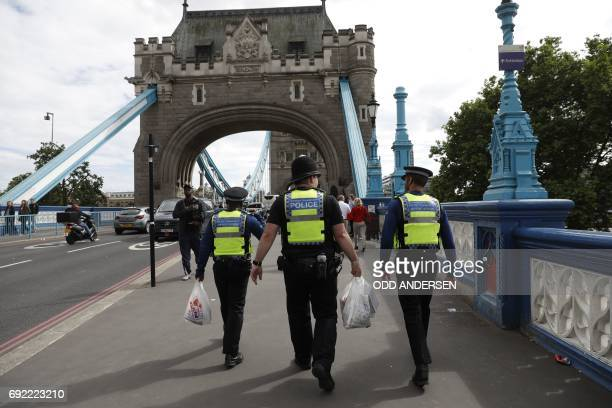 A British Transport Police officer and Community Support Officers walk along Tower Bridge in London on June 4 following a deadly terror attack at...