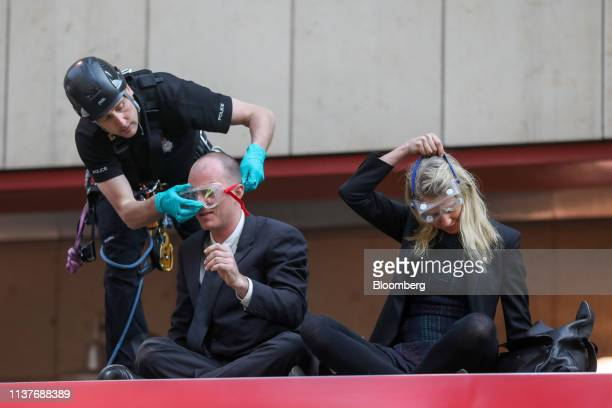 A British Transport Police officer secures protective eyewear to a climate activist who has attached himself to the top of a Docklands Light Railway...