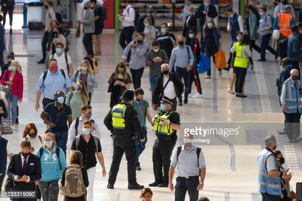 British Transport Police officers patrol on the concourse at London Waterloo railway station in London, U.K., on Monday, June 7, 2021. Flexible...