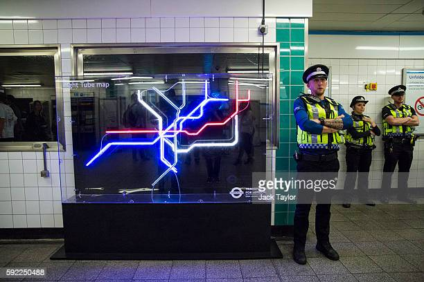 British Transport Police stand next to a neon installation of the Night Tube map in Brixton Underground Station on August 20 2016 in London England...