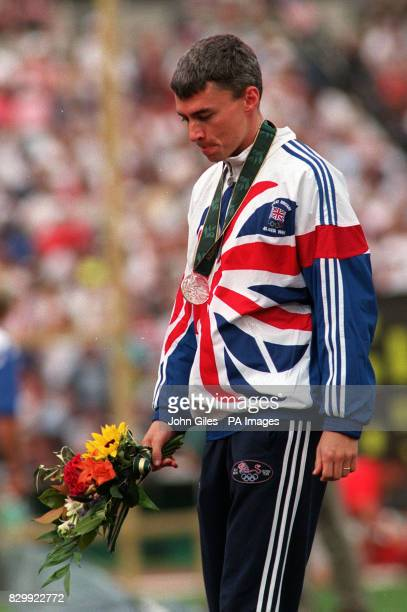 British triple jump world record holder Jonathan Edwards bites his lip as he leaves the Olympic Stadium Atlanta this evening with a silver medal...