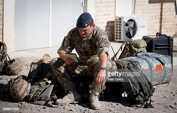 British troop reads as he begins his journey back home at Kandahar airfield on November 11 2014 in Kandahar Afghanistan Now that British combat...