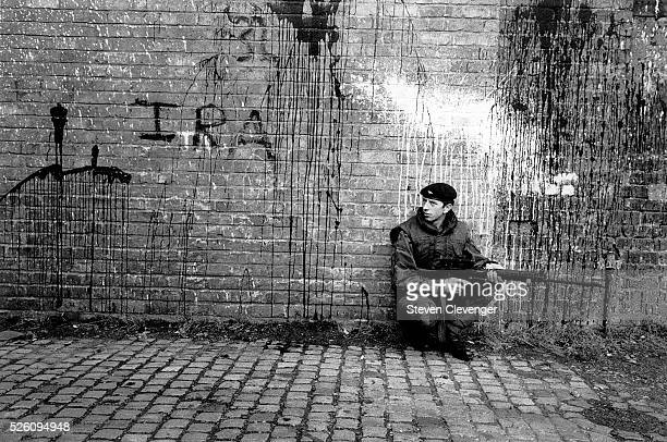 A British trooper sits beneath a graffiti covered wall while covering his comrades