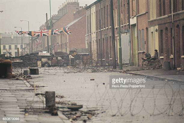 British troops and soldiers observe barricades of debris and barbed wire as union jack flags are displayed from terraced houses in the Shankill Road...