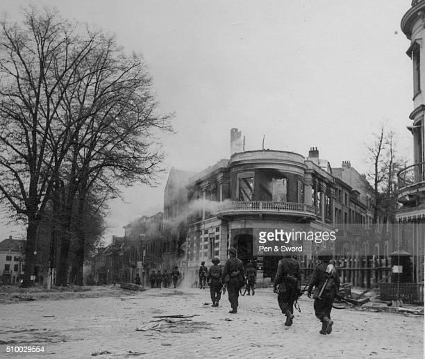 British troops in Arnhem next smouldering buildings France