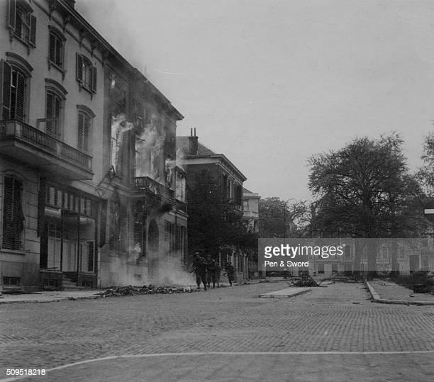 British troops in Arnhem running through burning street, France.