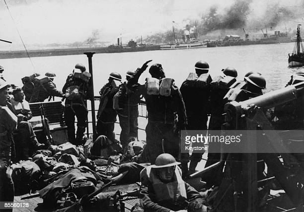 British troops look back at the French coast from the deck of a steamer which is taking them back to England after the evacuation of Dunkirk June 1940