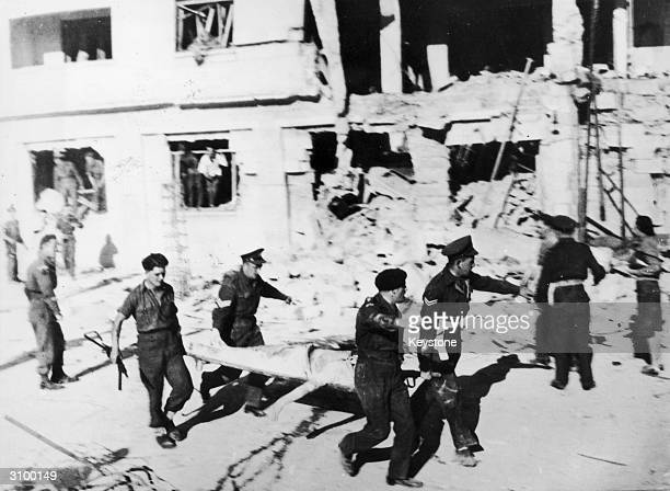 British troops taking away casualties after the Irgun Zvai Leumi Jewish terrorist/resistance group blew up Goldsmith Officers club in Jerusalem...