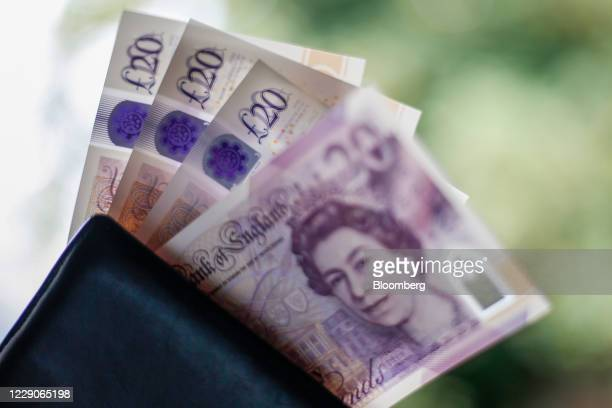 British twenty pound banknotes sit in a wallet in this arranged photograph in London, U.K., on Wednesday, Oct. 14, 2020. Pound traders are remarkably...
