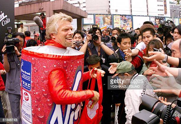 British tycoon Richard Branson hands out free colas in downtown Tokyo 23 April 1999 during a sales promotion for the Virgin Cola to break into the...