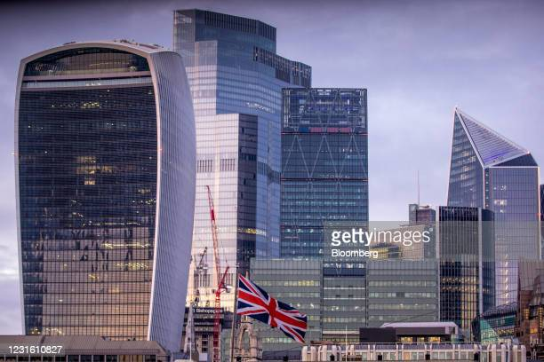 British Union flag, also known as a Union Jack, flies in view of skyscrapers in the City of London, U.K., on Monday, March 8, 2021. Values in the...