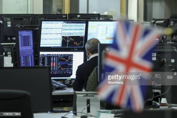 A British Union flag also known as a Union Jack hangs from a computer screen as a trader monitors financial data on computer screens on the trading...