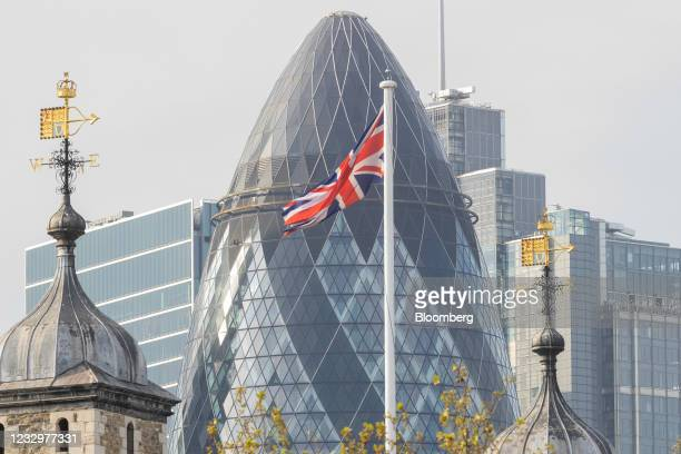 British Union flag, also known as the Union Jack, in view of skyscrapers and buildings including 30 St. Marys Axe, also known as The Gherkin, in the...
