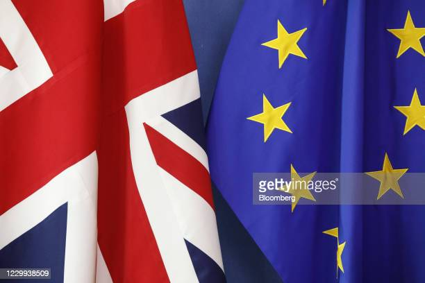 British Union flag, also known as the Union Jack, left, flag hangs beside a European Union flag ahead of the resumption of Brexit talks at the...