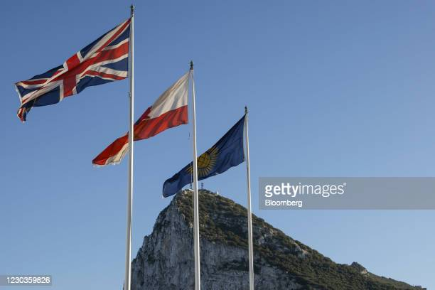 British Union flag, also known as the Union Jack, left, the Gibraltar flag, center, and the Commonwealth of Nations flag above the border crossing...