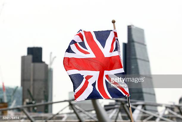 A British Union flag commonly known as a Union Jack flies from a pole against a backdrop of the Leadenhall building also known as the 'Cheesegrater...