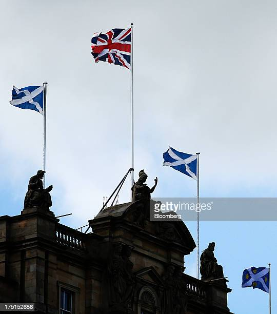 A British Union flag flies between Saltire flags the national flag of Scotland on top of the Bank of Scotland Ltd headquarters in Edinburgh UK on...
