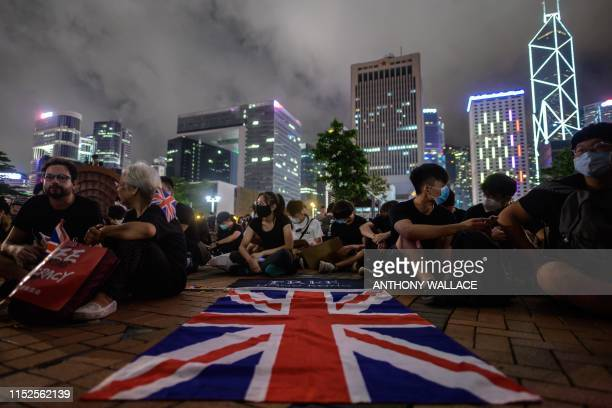 A British Union Jack flag is displayed as protesters gather along a fencedoff Victoria Harbour pier in Hong Kong late on June 28 before midnight when...