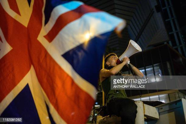 A British Union Jack flag is waved from the ground as a protester uses a loud hailer to speak outside the police headquarters in Hong Kong early on...