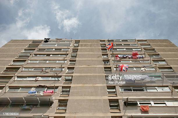 British Union Jack flags hang alongside drying clothes from the windows of a block of flats in the British Overseas Territory. A current diplomatic...