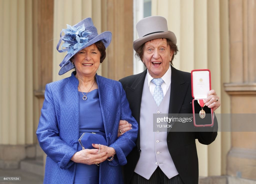 British veteran entertainer Ken Dodd (R) poses with his partner, Anne Jones (L), holding his medal after he was appointed a Knight Bachelor (knighthood) at an investiture ceremony at Buckingham Palace on March 2, 2017. / AFP PHOTO / POOL / Yui Mok