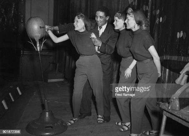 British vocal group the Beverley Sisters learn the essentials of boxing from World Middleweight Champion Randolph Turpin at the Trocadero Cinema in...