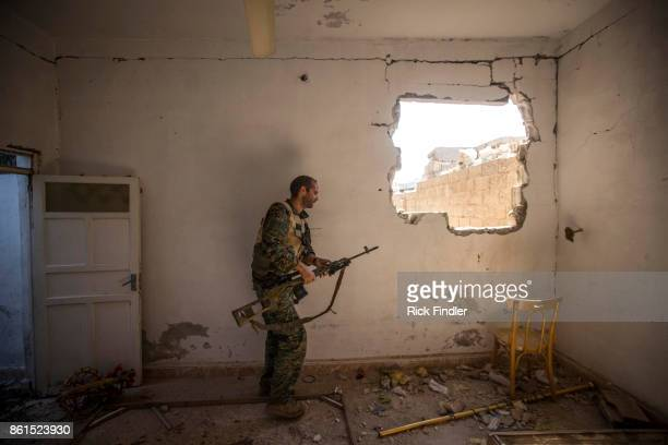 British volunteer fighter 'Macer Gifford' walks through an abandoned house as he tries to locate a spot to fire his sniper rifle toward ISIS...