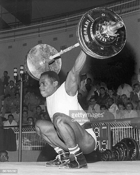 British weightlifter Louis Martin competing in the Middle Heavyweight event at the Rome Olympics, 12th September 1960. Martin eventually won the...