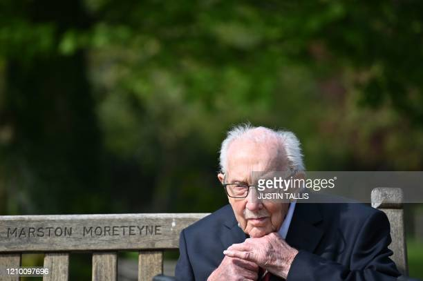 British World War II veteran Captain Tom Moore does up his tie as he sits on a bench in the village of Marston Moretaine 50 miles north of London on...